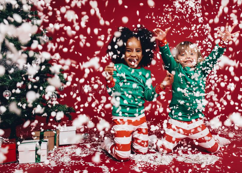 Two little girls in christmas costumes playing with artificial snow flakes. Kids having fun enjoying an artificial snowfall beside royalty free stock image