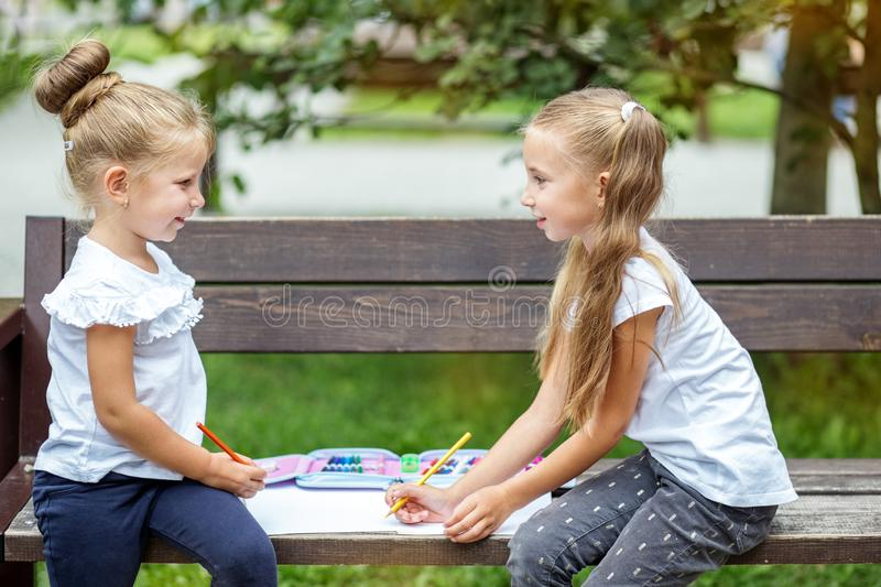 Two little girls draw in a school park. The concept of school, friendship, drawing, study, hobby.  royalty free stock photo
