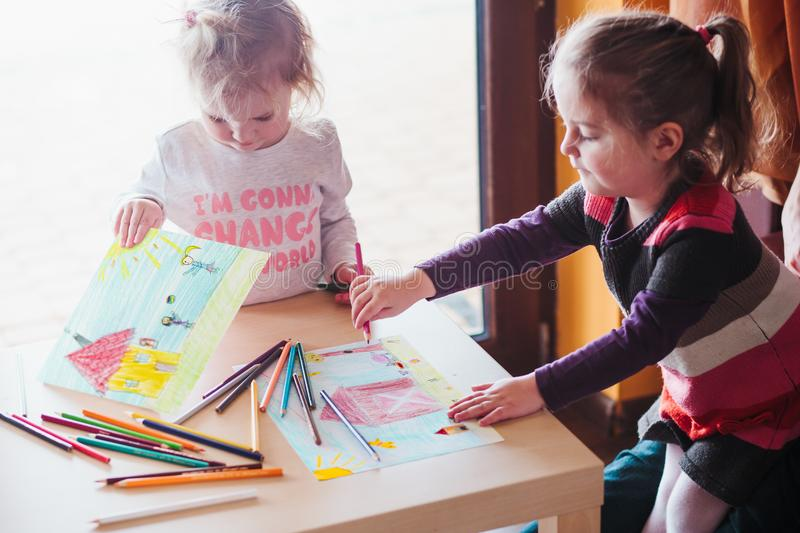 Two little girls drawing a colorful pictures using pencil crayon royalty free stock photo