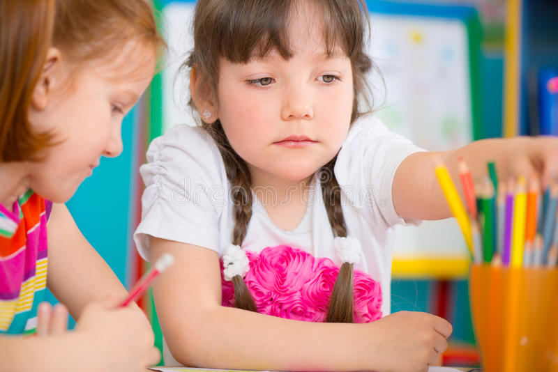 Two little girls drawing at kindergarten stock photography