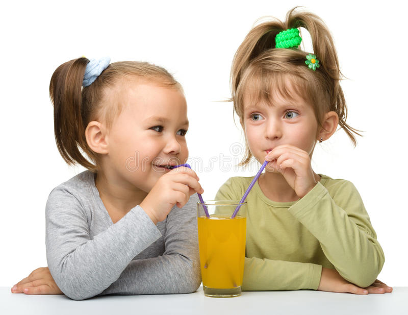 Two little girls are drinking orange juice stock image