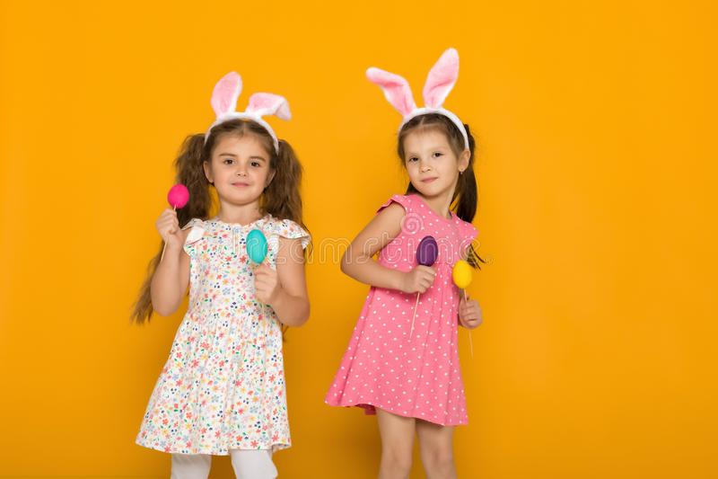 Little girls with Easter bunny ears holding colorful eggs stock photography