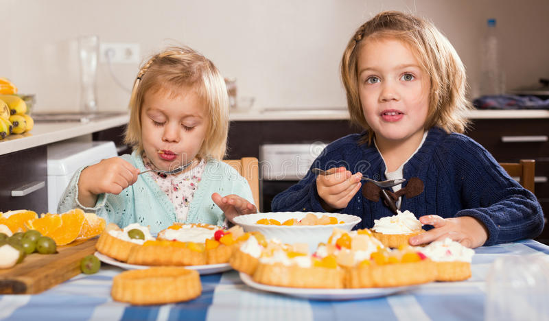 Two little girls enjoying pastry with cream royalty free stock photos