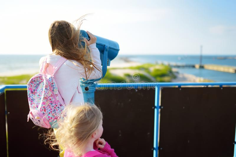 Two little girls enjoying a view of the Baltic sea shore at summer. Having fun in resort town of Ventspils. royalty free stock photos
