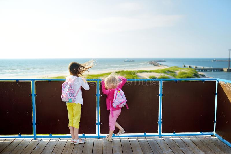 Two little girls enjoying a view of the Baltic sea shore at summer. Having fun in resort town of Ventspils. royalty free stock image