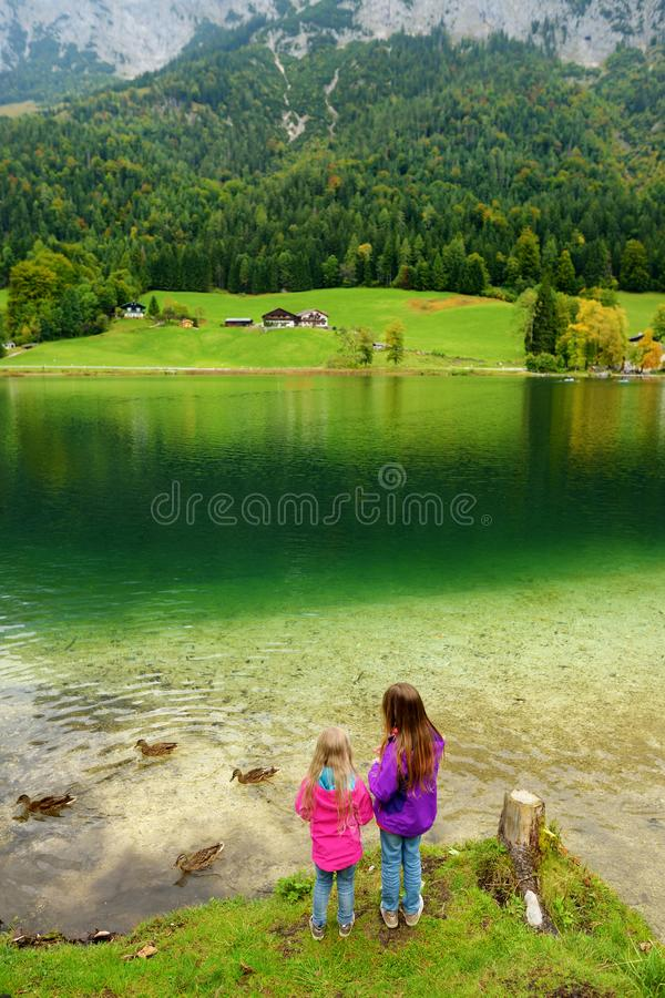 Two little girls enjoying the view of wonderful green waters of Hintersee lake. Amazing autumn landscape of Bavarian Alps on the A stock images