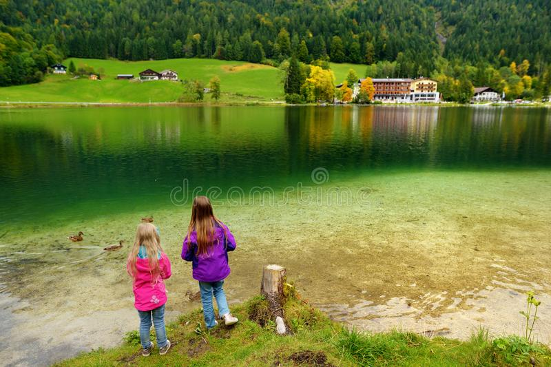 Two little girls enjoying the view of wonderful green waters of Hintersee lake. Amazing autumn landscape of Bavarian Alps on the A royalty free stock photography