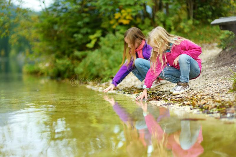 Two little girls enjoying the view of wonderful green waters of Hintersee lake. Amazing autumn landscape of Bavarian Alps on the A royalty free stock images
