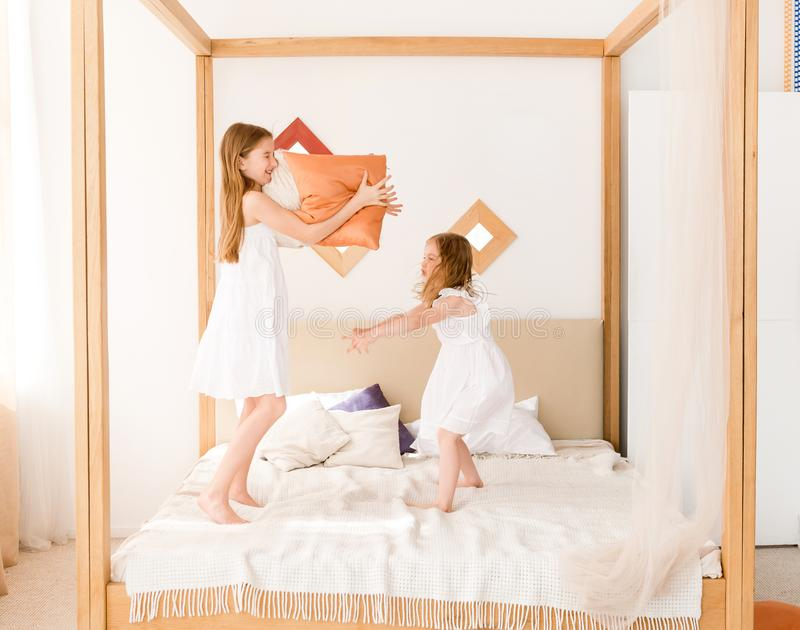Two little girls fighting with pillows on the bed stock image