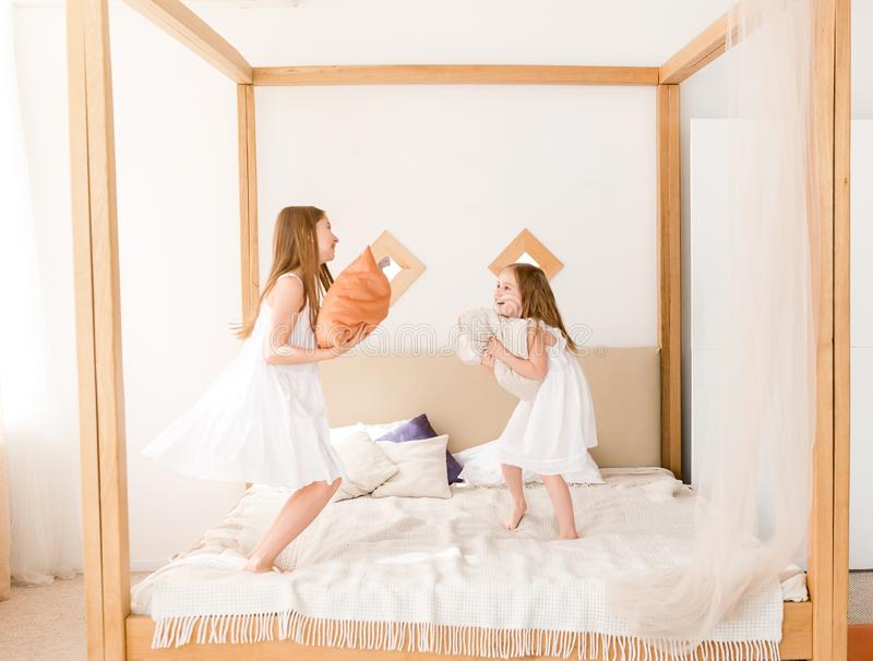 Two little girls fighting with pillows on the bed stock images