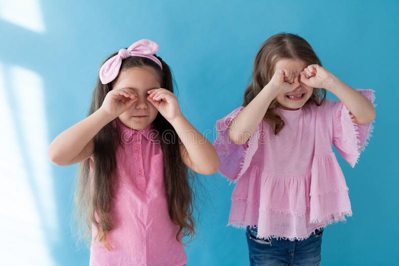 Two little girls girlfriends sisters portrait on a blue background stock photography