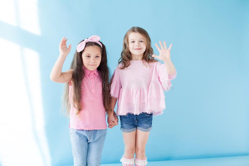 Two little girls girlfriends sisters portrait on a blue background stock photos