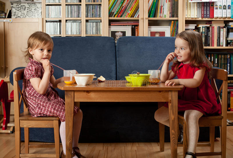 Two little girls have a breakfast at home. Two little smiling girls have a breakfast at home royalty free stock photo