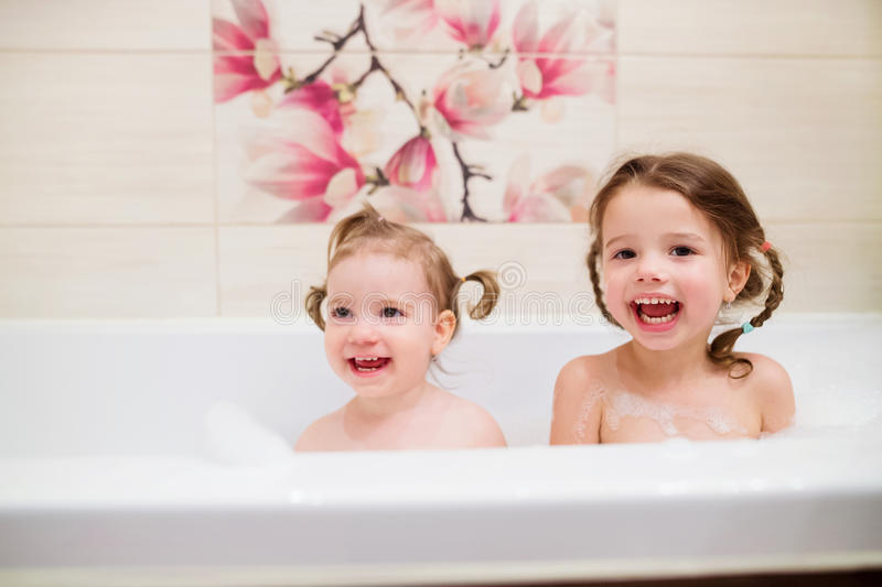 Two little girls having bath with bubbles in bathtub royalty free stock photos