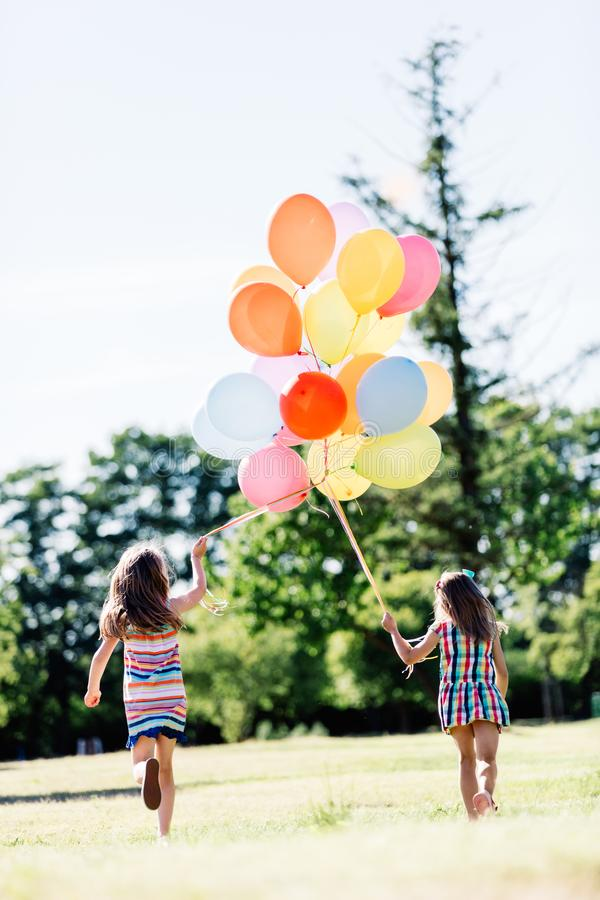 Two little girls holding a bunch of balloons together. royalty free stock photo