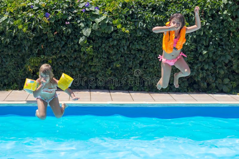 Two little girls jumping together in the pool; positive emotions, summer and fun royalty free stock photography