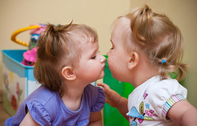 Two little girls kissing. Two cute little girls kissing and showing affection royalty free stock photography