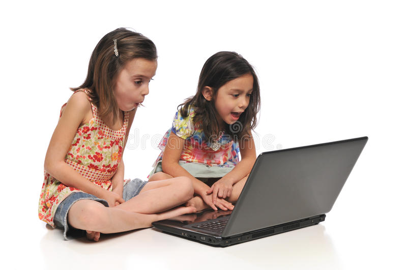 Two little girls with a laptop computer. Isolated on a white background stock images