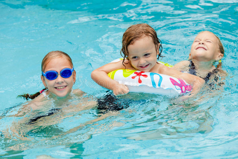 Two little girls and little boy playing in the swimming pool. At the day time stock image