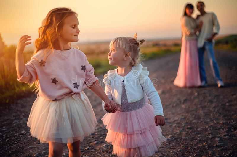 Two little girls look at each other, walk down the road and hold hands outdoors at sunset. stock photography