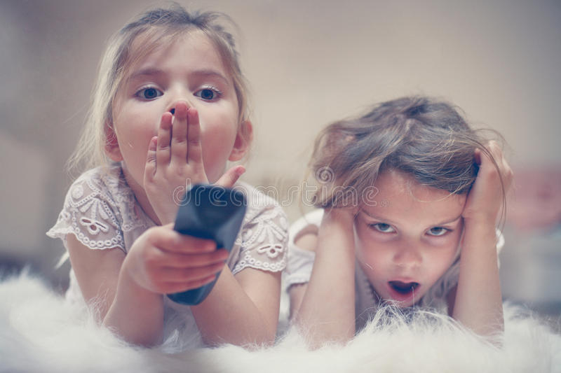 Two little girls lying on the floor. Two sisters lying on the floor and watching something boring on TV stock image
