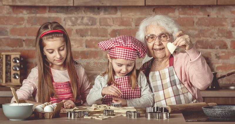 Little girls making cookies with her granny royalty free stock image