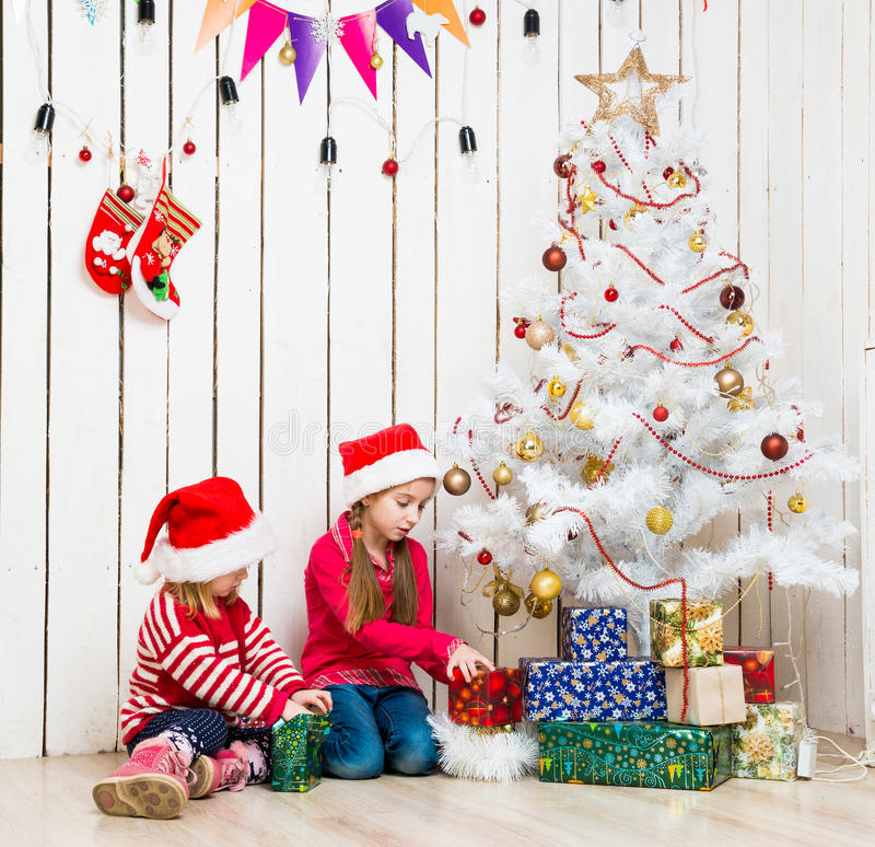 Two little girls open christmas presents sitting on the floor royalty free stock photos