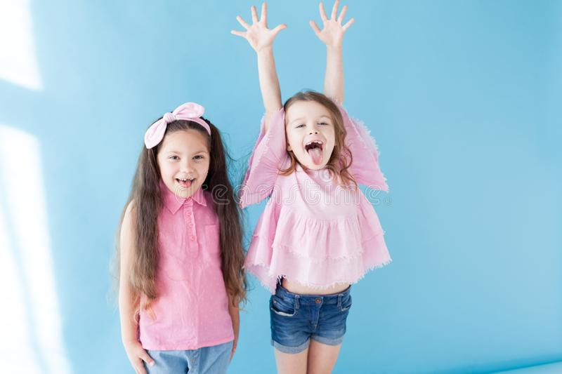 Two little girls in pink clothing girlfriends laugh. Two little girls in pink clothing girlfriends hold hands royalty free stock image
