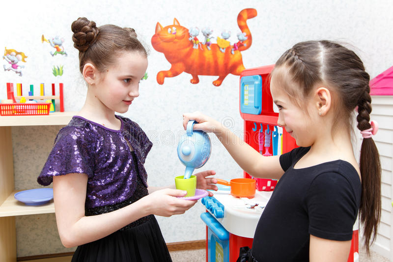 Two little girls play role game with toy kitchen in day care center. Indoors stock photography