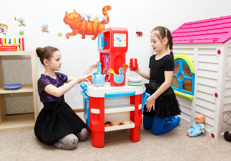 Two little girls play role game with toy kitchen in day care. Center indoors royalty free stock photography
