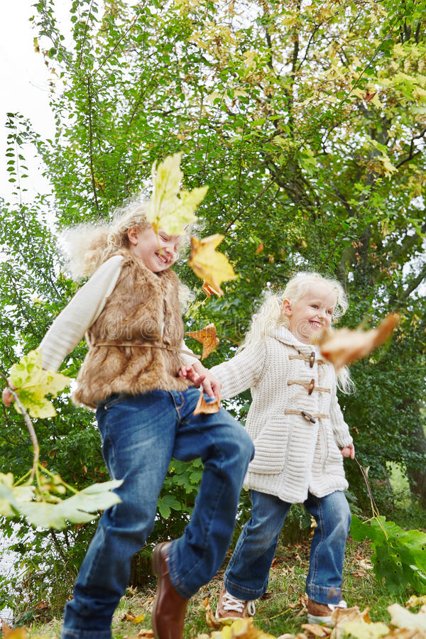 Two little girls playing with autumn leaves royalty free stock photo