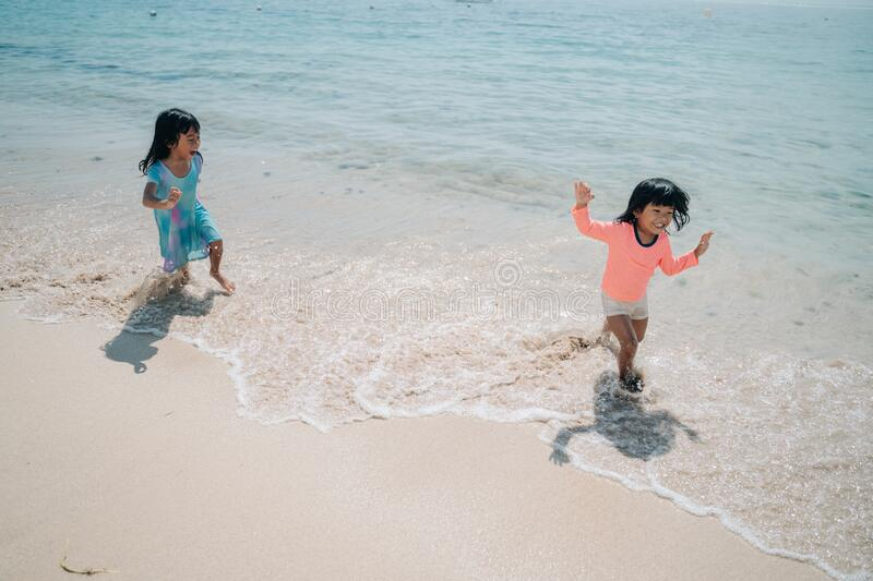 Two little girls playing chase in the beach. Two little girls playing chase each other when enjoy playing together in the beach royalty free stock images