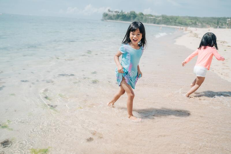 Two little girls playing chase in the beach. Two little girls playing chase each other when enjoy playing together in the beach royalty free stock image
