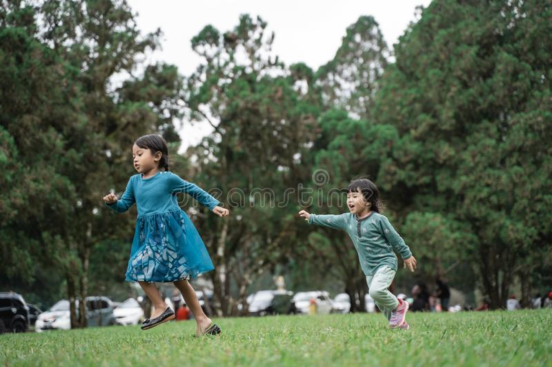 Two little girls playing chase each other. When enjoy playing together in the park royalty free stock images