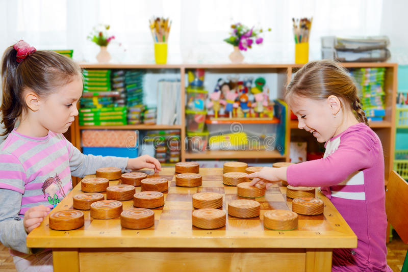 Two little girls playing in checkers stock image