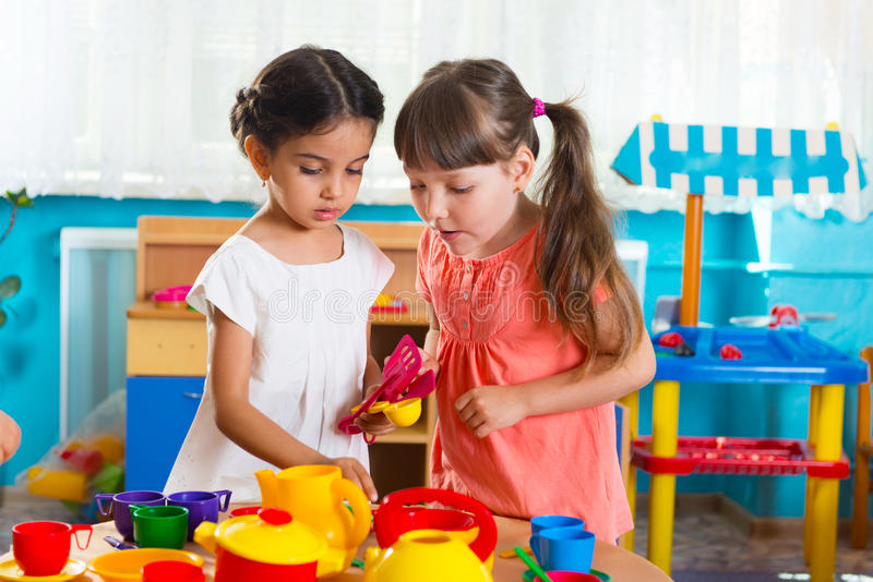 Two little girls playing in daycare. Two cute little girls playing role game in daycare royalty free stock photo
