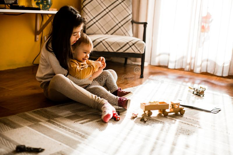 Two little girls playing on the floor in room royalty free stock photo