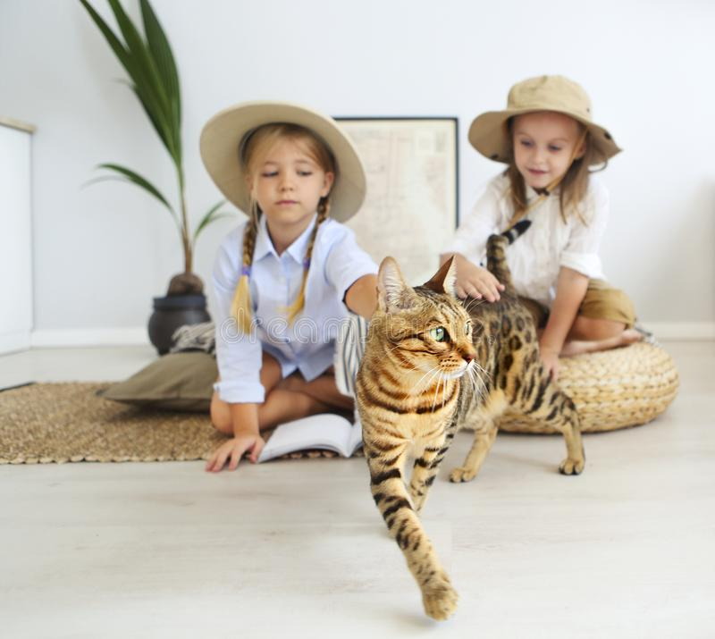 Two little girls are playing at home to travelers with bengal cat wearing vintage style clothes. Childhood, fantasy, imagination royalty free stock photos