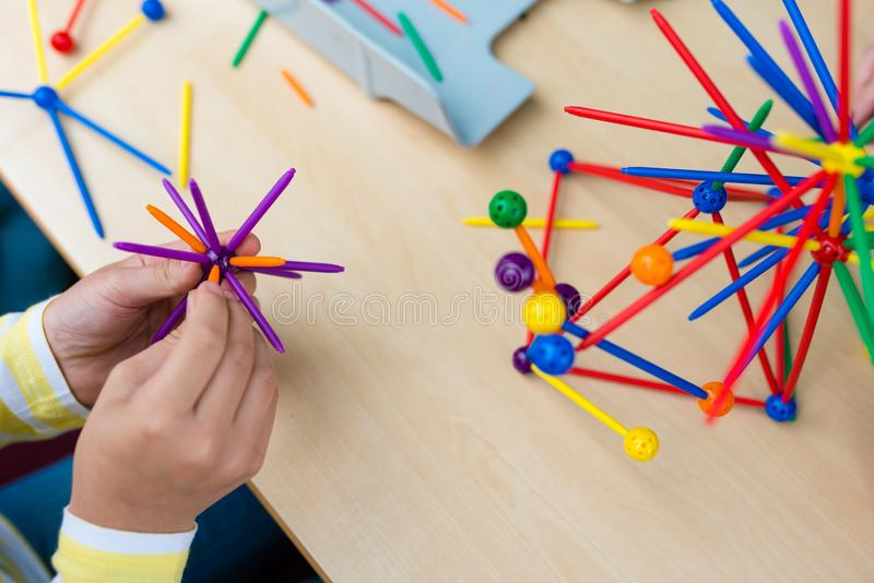 Two little girls playing with lots of colorful plastic sticks kit indoors. kids having fun with building geometric figures and l stock photography