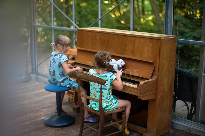 Two little girls playing the piano royalty free stock photos