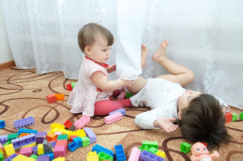 Two little girls playing. Sisters - baby and toddler play constructor toys stock photography