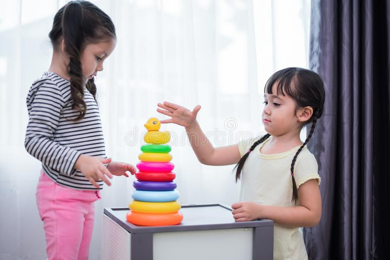 Two little girls playing small toy balls in home together. Education and Happiness lifestyle concept. Funny learning and Children royalty free stock photo