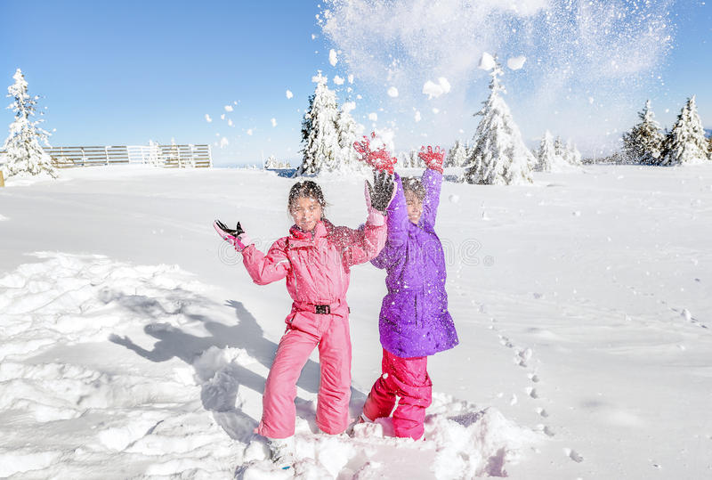 Two Little girls playing with snow and having fun stock photography