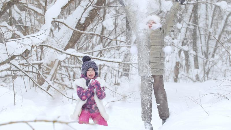 Two little girls playing with snow in winter forest. royalty free stock photo