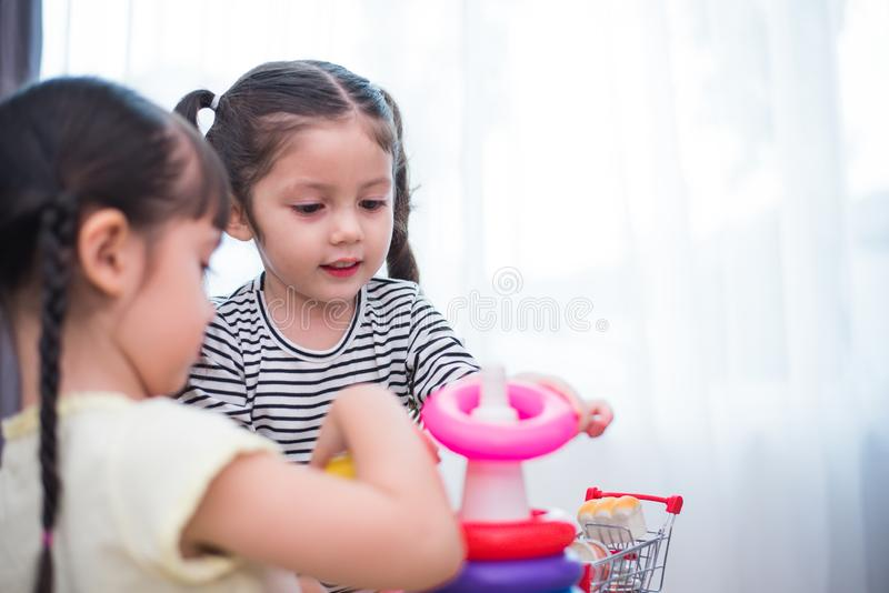 Two little girls playing toy hoops in home together. Education and Happiness lifestyle concept. Funny learning and Children. Two little cute girls playing toy stock images