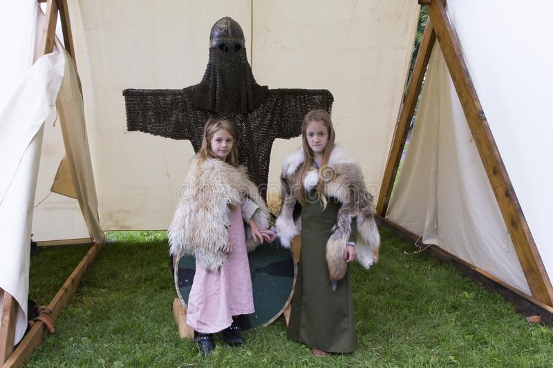 Two little girls posing in medieval costume in tent with coat of mail during the Celtic Festival held in Domaine de Maizerets stock photography