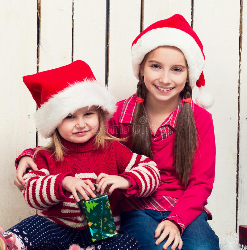 Two little girls in red hats sitting on the floor with gifts stock photography