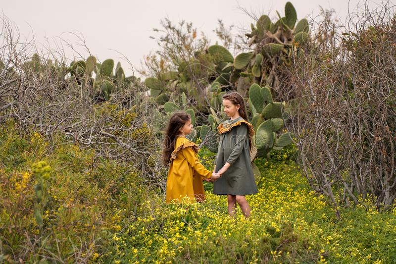 Two little girls in retro vintage dresses holding hands stand in cactuses and overgrown branches stock photo