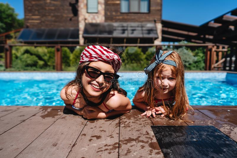 Two little girls on the side of the pool stock photo