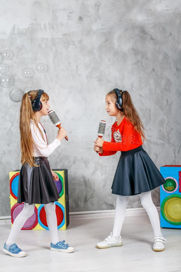 Two little girls sing and dance. The concept is childhood, lifestyle, dance, music. stock photo